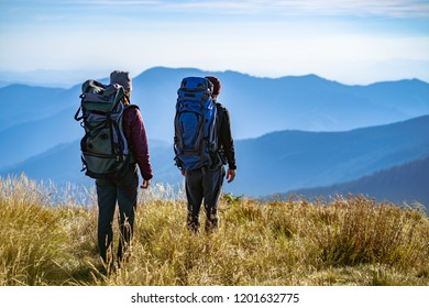 The man and a woman standing on the mountain with a beautiful view