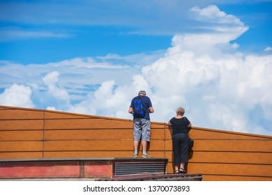 A man and a woman standing on the observation deck in Batumi.  Wooden fence on the background of the cloudy sky. Rest in Georgia.
