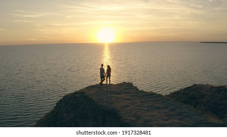The man and woman standing on the rocky sea shore