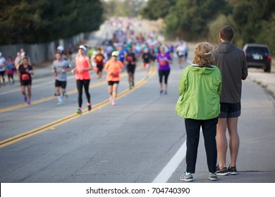 Man and woman standing on the side of a street during a local marathon and cheering on runners