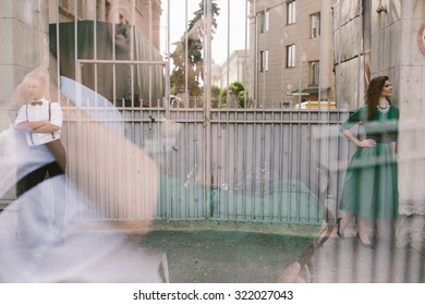 man and woman standing on the street on the opposite sides of the gate