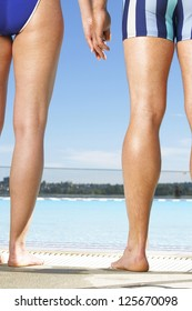 Man and woman standing side by side alongside a pool in bathing costumes cropped so that only one leg of each is visible