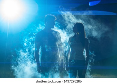 The man and woman standing in the smoke on a bright light background