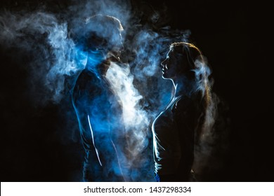 The man and woman standing in smoke on the dark background