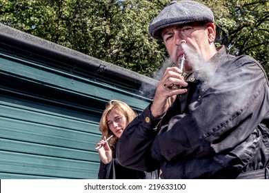 Man and woman standing smoking e-cigarettes outdoors with a lowe angle view off the middle-aged man exhaling smoke from his nostrils in the foreground