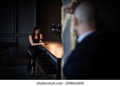Ein Mann und eine Frau, bleibt aus dem Film. Eine schöne Brünette in einem schwarzen Kleid sitzt an der Bar und trinkt Wein, und eine Pistole liegt neben ihr, ein kahler Mann sieht sie an. Valentinstag