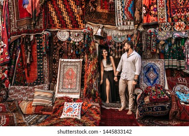 Man and woman in the store. Couple in love in Turkey. Man and woman in the Eastern country. Happy couple travels the world. Persian shop. Tourists in store. Oriental carpet. Istanbul. Follow me