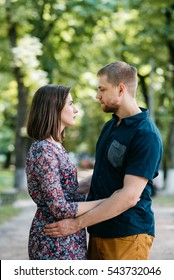 Man and woman in summer clothes look at each other seriously while they hug