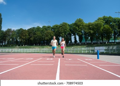 Man and woman sunny outdoor on blue sky. Coach and trainer at workout. Sport and healthy fitness. Runner on competition and future success. Couple running on arena track.