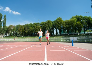 Man and woman sunny outdoor on blue sky. Sport and healthy fitness. Coach and trainer at workout. Couple running on arena track. Runner on competition and future success.