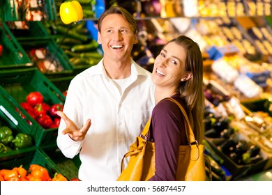 Man and woman in a supermarket at the vegetable shelf shopping for groceries, he is tossing a bell pepper and seems to be full of joy