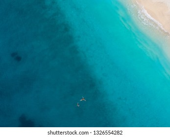 Man and a woman swimming in the clear and transparent turquoise water of Mediterranean sea. Aerial top down shot