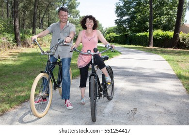 A man and a woman take advantage of the holidays to go cycling in summer