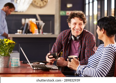 Man and woman talking at a coffee shop