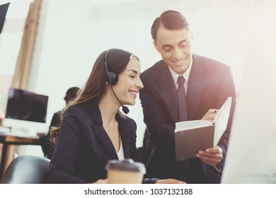 A man with a woman talking to each other in the office. They are both operators of the call center. They are in a good mood.