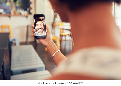 Man and woman talking to each other through a videochat on a mobile phone. Woman having a video call with man on her smart phone. Woman sitting at a coffee shop.