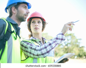 Man and woman, talking in hard hats