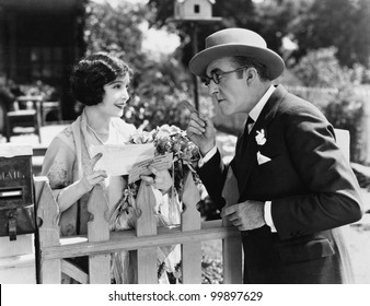 Man and woman talking over a picket fence