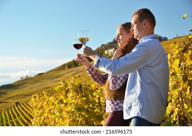 Man and woman tasting wine among vineyards in Lavaux, Switzerland