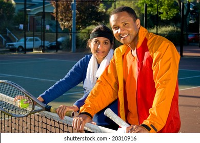 Man and woman tennis players smiling  as they stand at the net. They are holding rackets. Horizontally framed photo.