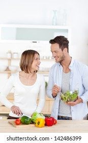 Man and woman in their Kitchen at home preparing vegetable salad