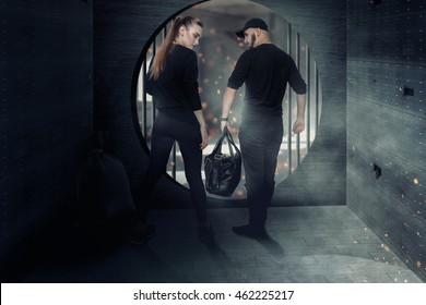 man and woman thieves robbed the bank and leave the warehouse with a bag full of money. Blockbuster photo of a young couple of thieves in a bank with money