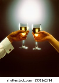 a man and a woman, toast with white wine over dark background
