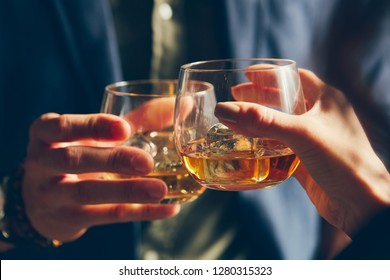 Man and woman toasting with glasses of whisky in a sunlight