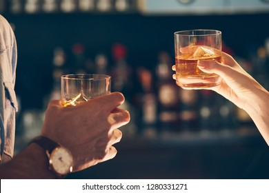 A man and a woman toasting with glasses of whisky in a bar with sunlight hitting their hands