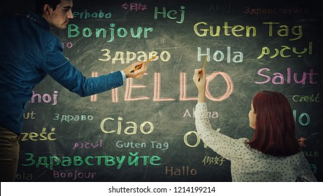 Man and woman together drawing word hello in different languages and colors on blackboard. Opportunity for learning many languages for students. Business partnership and teamwork concept.