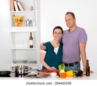 man and woman together in the kitchen