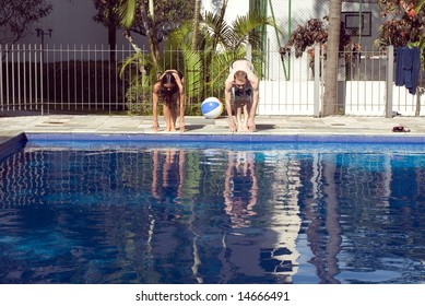 A man and a woman are together at a pool.  They are about to dive into the water.  They are looking down at the water.  Horizontally framed photo.