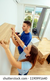 Man and woman together putting shelf in their apartment. Young family decorating and moving in