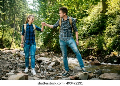 Man and woman tourists walking hand in hand through the woods in the mountains