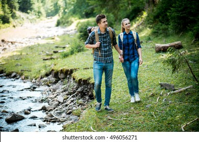 Man and woman tourists walking hand in hand through the woods in the mountains by the river