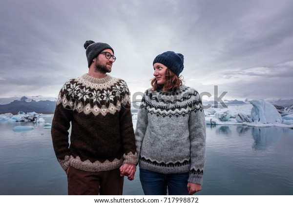 Man and woman in traditional handmade sweaters holding hands in front of glacier lagoon in Iceland