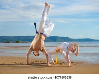 A man and a woman to train capoeira on the beach - concept about people, lifestyle and sport.