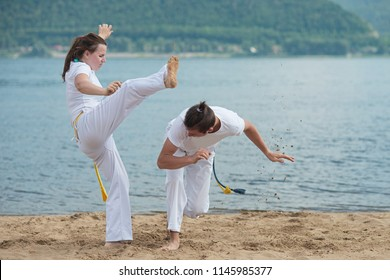 Man and woman train capoeira on the beach - concept about people, lifestyle and sport. Training of two fighters