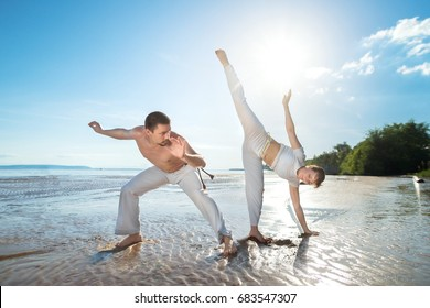 A man and a woman train capoeira on the beach - concept about people, lifestyle and sport.