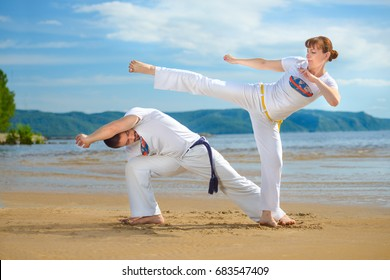 A man and a woman to train capoeira on the beach. - concept about people, lifestyle and sport. Male coach of capoeira trains his pupil. Man and woman play staged fight.