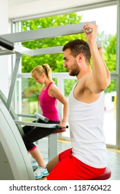 Man and woman train on machine in a fitness club or gym