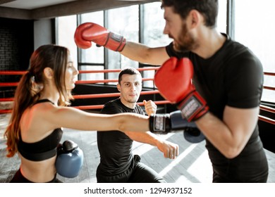 Man and woman training to box with personal coach on the boxing ring at the gym