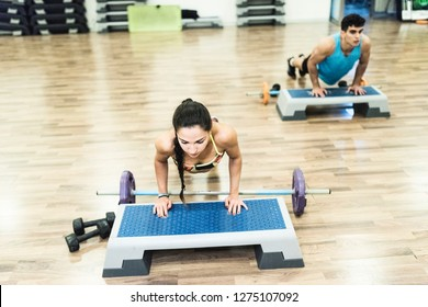 Man and woman training in gym class push ups