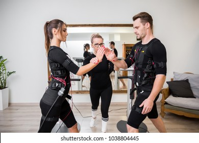 Man and woman training muscles with ems devices