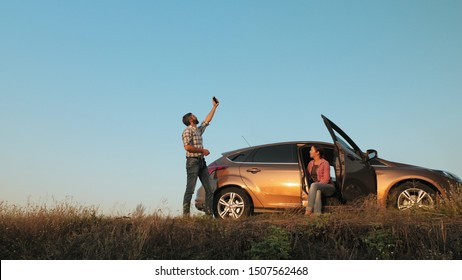 Man and woman traveling by car catches a phone signal while standing on the side of the road