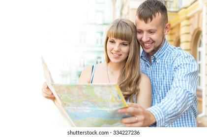 Man and woman traveling. Young couple doing a tour of the city. See on the map, city plan. Discuss your future route path. Concept - couple with map in the old city. Holiday and tourism. Summer day.