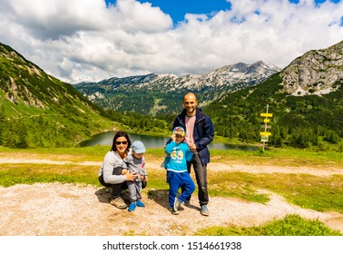 Man, woman and two young kids standing close by a valley with view to the Gross lake and high Alp mountains in the Tauplitzalm on a cloudy day on circa July 2019 in Tauplitz, Austria.