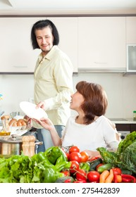 Man and woman with vegetables in kitchen at home