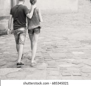 A man and a woman walk along the pavement, he holds her by the neck
