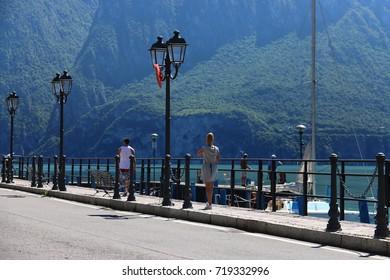 Man and woman walk along the promenade Lake Iseo, Riva di Solto Italy, 17 June 2017
